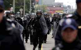 Police wearing full riot gear, walk north on Pape Ave., near the temporary G20/G8 detention centre in Toronto.