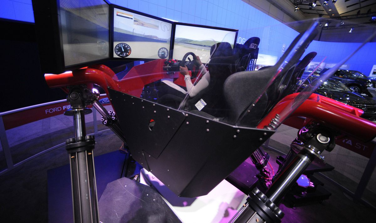 People try out the Ford Focus simulator during the media preview of the Canadian International Auto Show in Toronto.