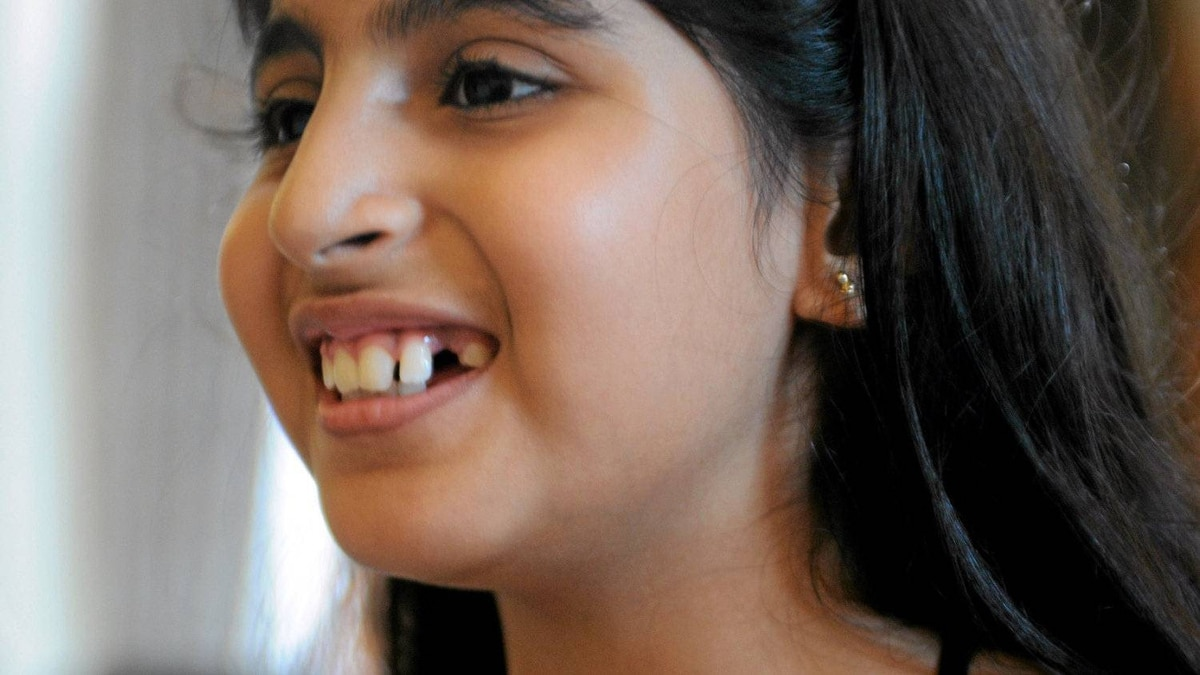 """Danya Sethy, 10, shows the gap in her teeth. Danya had two of her """"milk teeth"""" removed in order to bank them for stem cells."""
