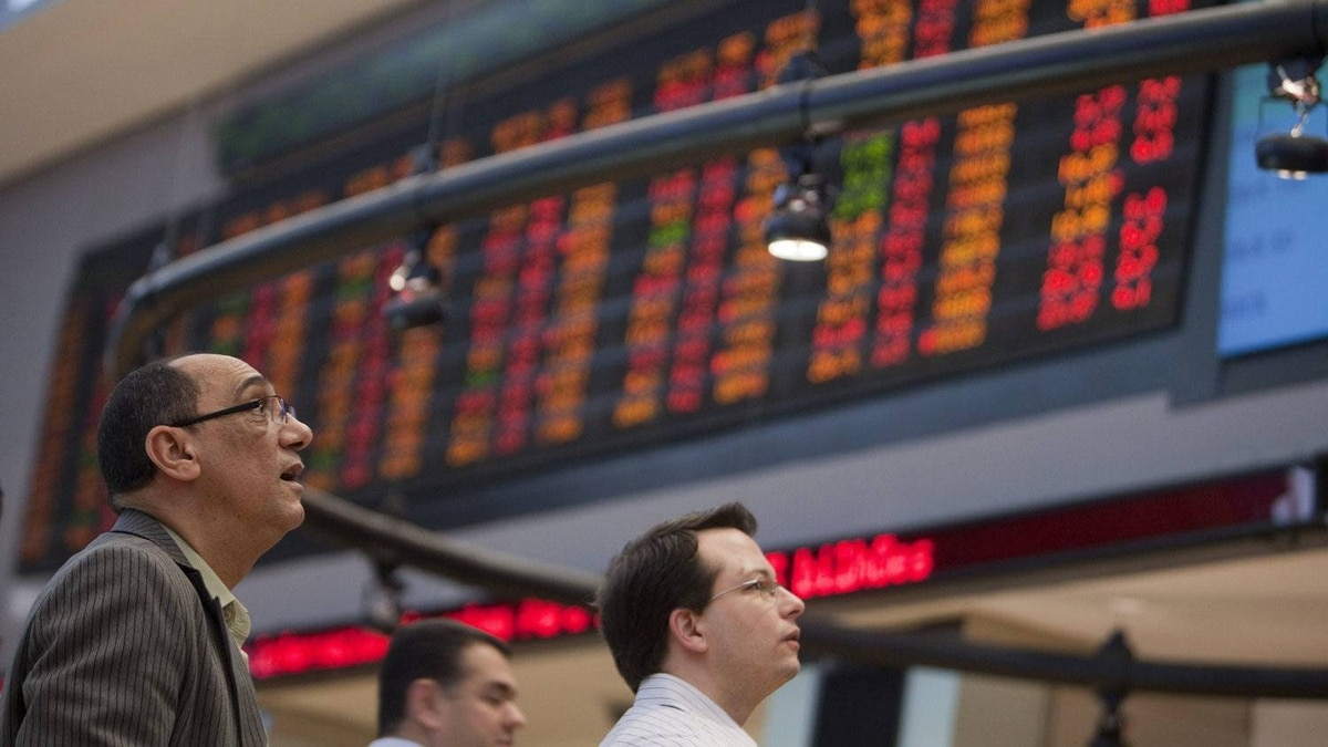 Visitors look at monitors at the stock market in Sao Paulo, Brazil, , Aug. 8, 2011.