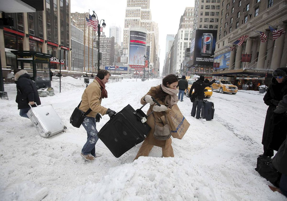 Travellers carry their luggage through a snow bank on 7th Avenue in front of Penn Station after a snow storm in New York