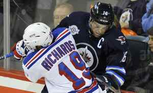 New York Rangers' Brad Richards (19) checks Winnipeg Jets' Andrew Ladd into the boards during the first period of their NHL game in Winnipeg, October 24, 2011.
