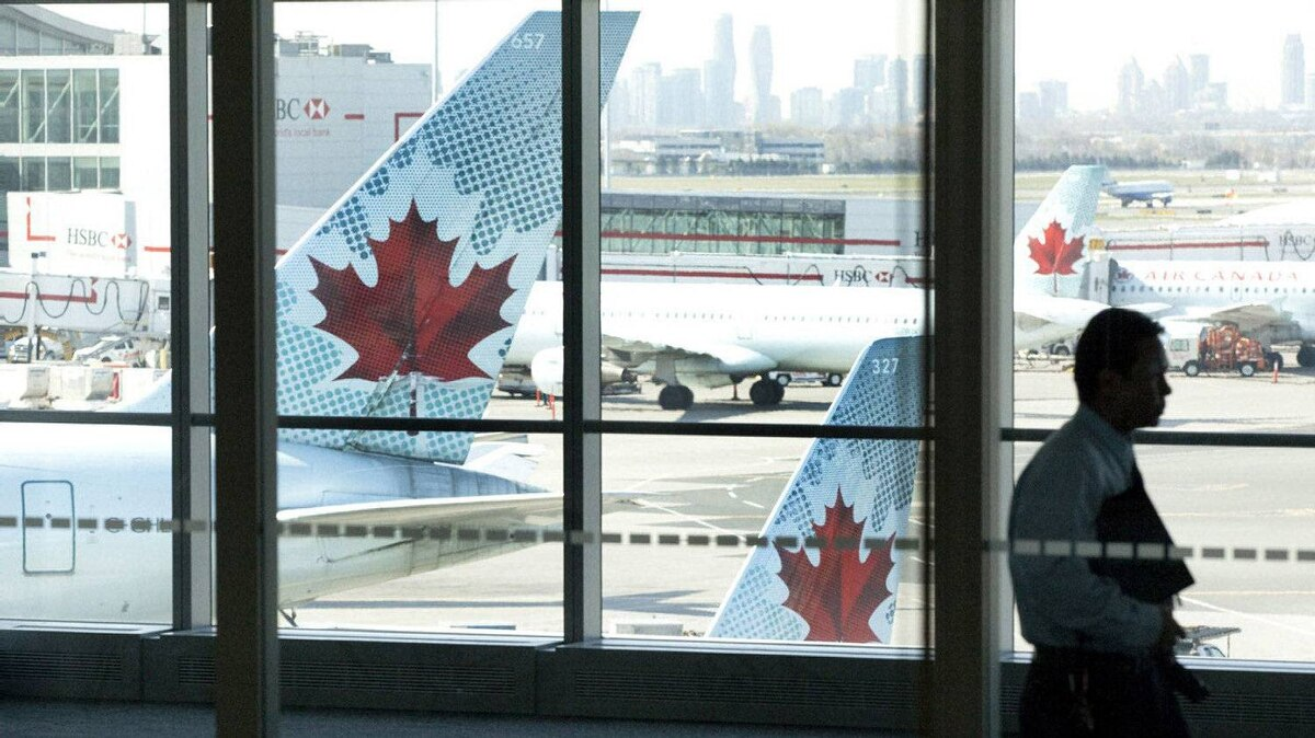 A person walks by Air Canada planes at Toronto Pearson Airport on Friday, April 13, 2012.