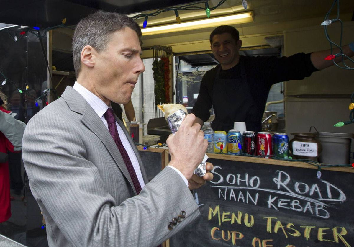 Vancouver Mayor Gregor Robertson, left, takes a bite of a vegetarian naan wrap prepared by Sarb Mund, right, at his Soho Road food truck outside City Hall in Vancouver, B.C. Twelve new street food vendors will be eligible to begin doing business on May 1.