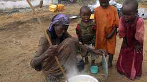 A woman from southern Somalia prepares food as her children watch at a camp for internally displaced people in Mogadishu, Somalia, on Wednesday, July 13, 2011.