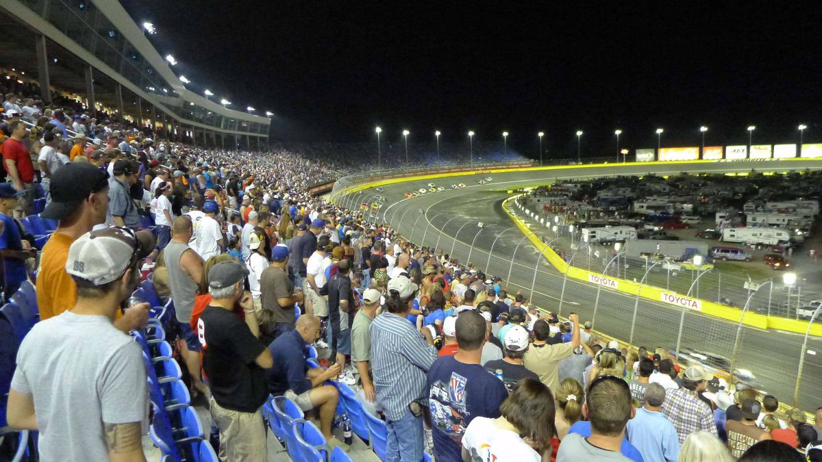 Packed grandstands for the 2011 NASCAR All-Star race at Charlotte Motor Speedway. Cars lap the banked track at over 200 miles per hour.