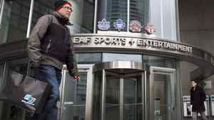 Pedestrians walk past the Maple Leaf Sports and Entertainment offices in Toronto on March 13, 2011.