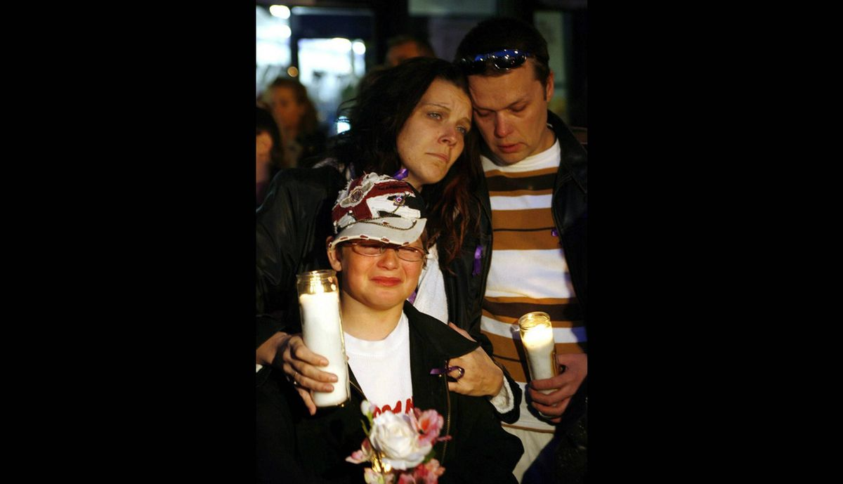 Victoria Stafford's mother Tara McDonald hugs her son Daryn, and partner James Gorris at a community candlelight vigil on the fourth day of the search for then-missing eight-year-old in Woodstock, Ontario, Sunday, April 12, 2009.