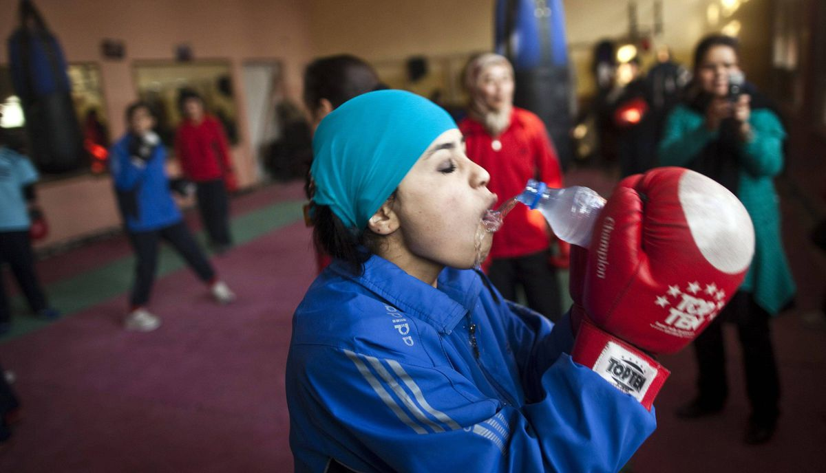An Afghan woman drinks water during a practice session inside a boxing club in Kabul December 26, 2011.