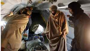 Saif al-Islam Gaddafi (2nd R) is pictured standing in a plane in Zintan November 19, 2011. Saif al-Islam Gaddafi told Reuters on Saturday that he was feeling fine after being captured by some of the fighters who overthrew his father and he said injuries to his right hand were suffered during a NATO air strike a month ago.