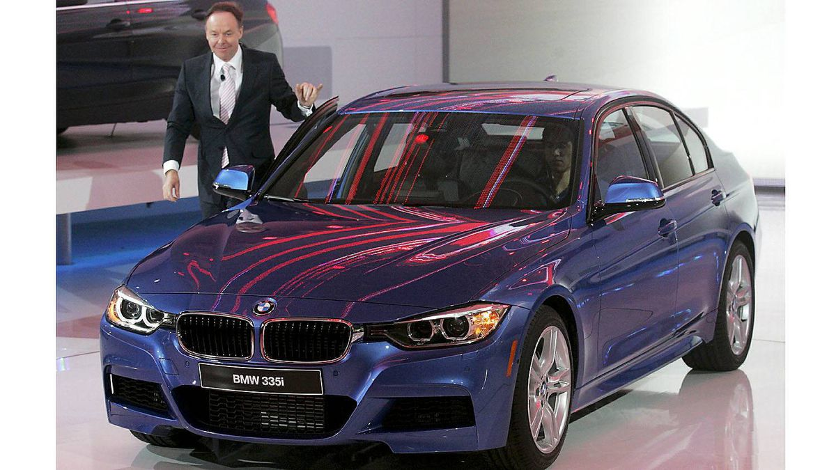 BMW Board Member Ian Robertson stands next to the new 2013 BMW 335i.