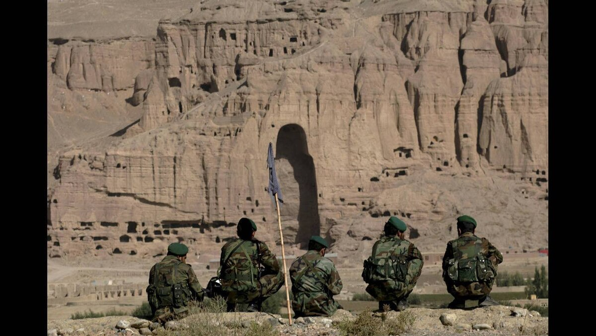 Afghan soldiers sit on a ledge overlooking the valley of Bamian in central Afghanistan, September 22, 2005.