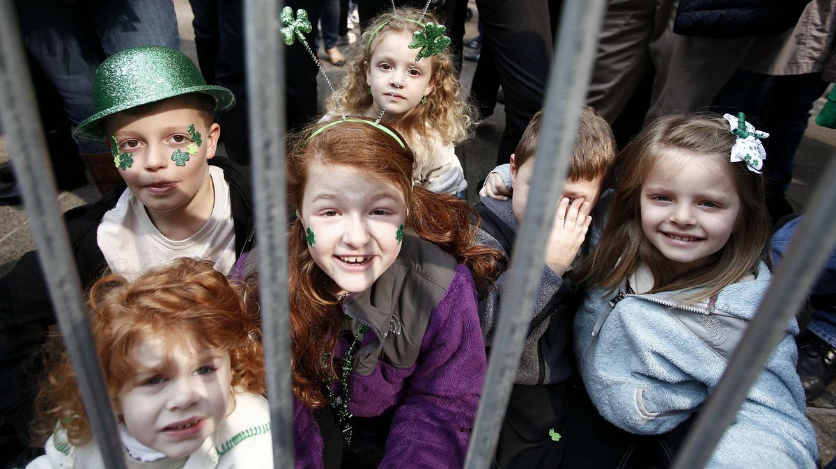 Children sit behind the barricade during the New York parade on Saturday.