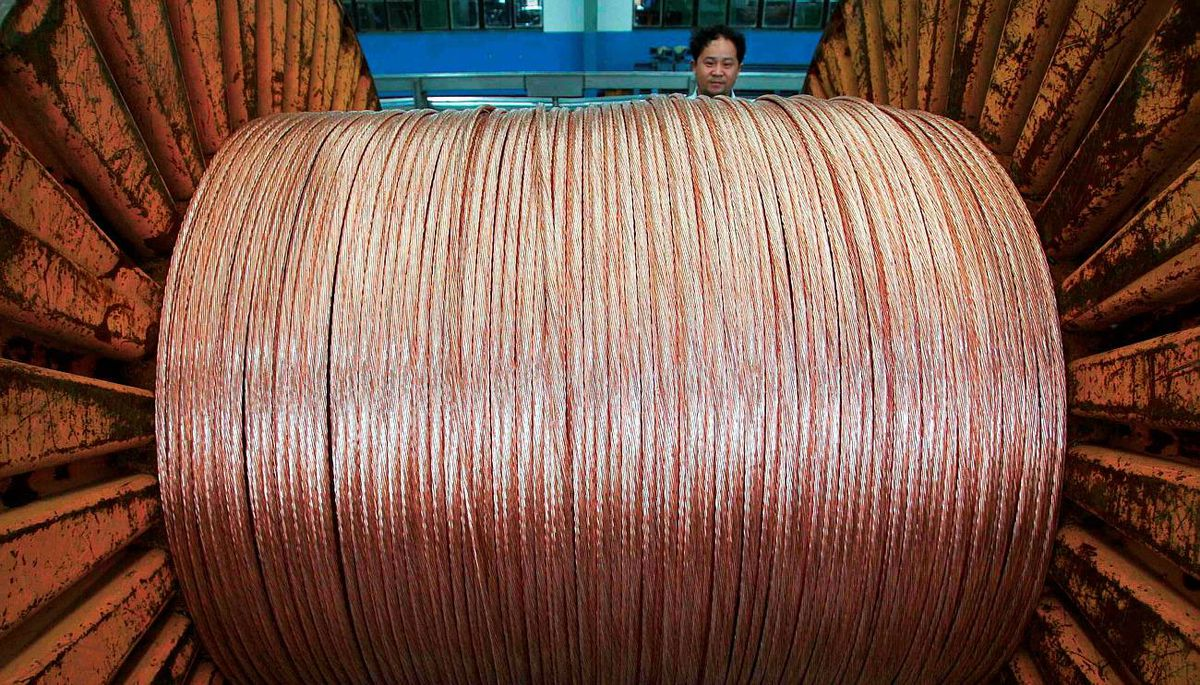 An employee works with a reel of copper cable at a factory in China.