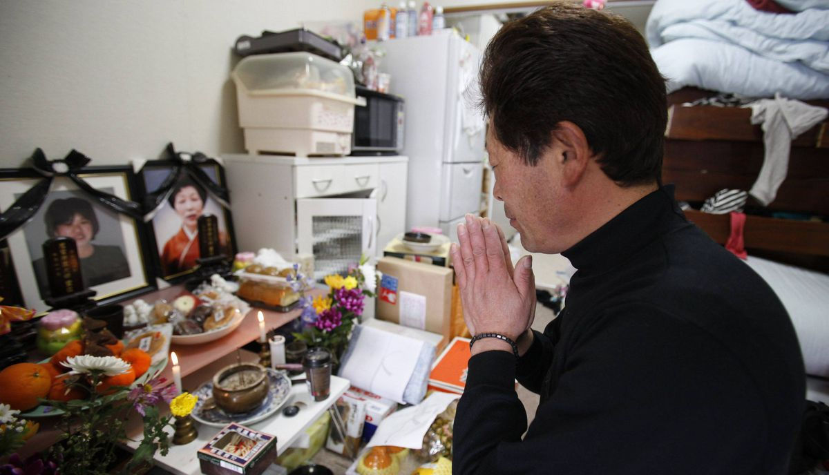 Takaaki Watanabe prays in front of portrait photos of his late wife Yukiko and his mother Kyoko, in his temporary house in Minamisanriku town, in Miyagi prefecture, northeastern Japan February 24, 2012. Watanabe, a seaweed farmer, was one of the lucky 5.8 percent from his hometown whose boat survived the March 11, 2011 tsunami, however what he lost was much greater. Tsunami waves swept away his wife, mother and his house, that was built on land handed down to him through 13 generations.