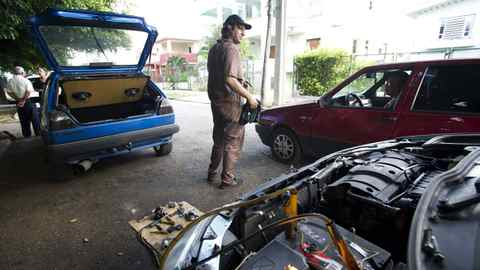 Lazaro Rafael, 31, repairs cars on the street outside his home in Havana, Cuba Sept. 30, 2011. Rafael specializes in fixing the newer European and Asian made cars that have become more prevalent in Cuba in recent years.