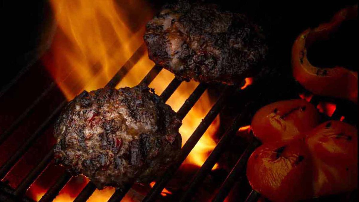 Hamburgers with sundried tomato and cumin grilling on the barbecue.