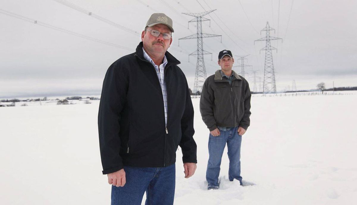 John Wilkin on his property near Walkerton, Ont., with hydro towers looming nearby. With him is his son Greg.