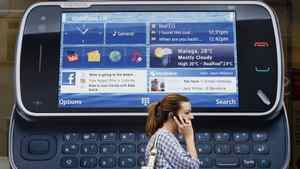 A woman uses her mobile telephone as she passes a Nokia advert in London, in this file picture taken July 20, 2009.