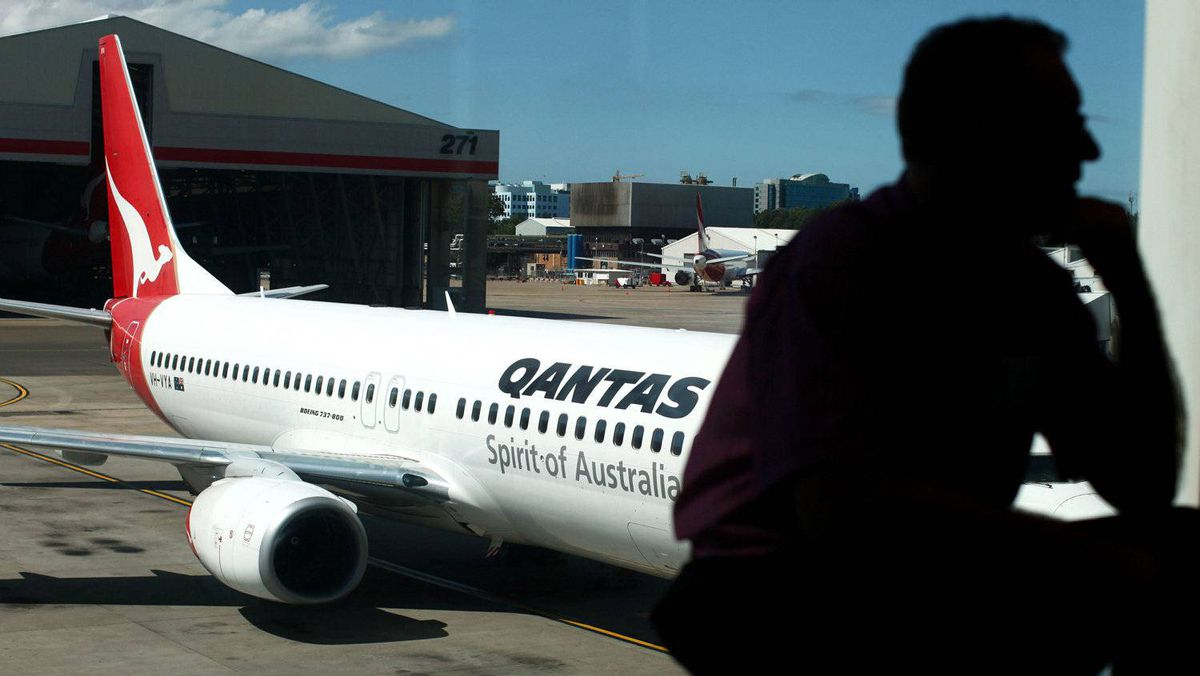 In a file picture taken on Oct. 31, 2011, a passenger waits for Qantas flights to resume service at Sydney International airport.