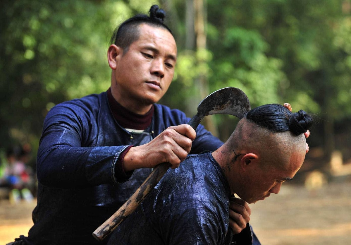 A member of the Miao ethnic minority shaves another villager's head with a sickle in the village of Basha in Congjiang county, Guizhou province, China.