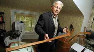 Paul Beazley , Mayor of Windsor and member of Hockey Museum Board of Directors holds a hockey stick which was hand crafted by the Mi'kmaq first nations at the hockey museum in Windsor, Nova Scotia.