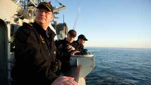 Commander Richard Dowker, Sub-Lieutenant Paul Mercer, and Lieutenant Scott Dyson stand watch from the port bridge wing of HMCS Winnipeg.