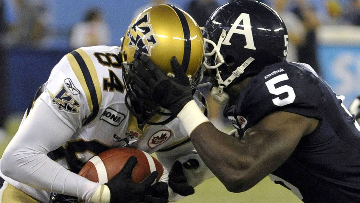 Toronto Argonauts defensive end Ejiro Kuale grabs hold of Winnipeg Blue Bombers wide receiver Greg Carr (L) during the first half of their CFL football game in Toronto September 24, 2011. REUTERS/Mike Cassese
