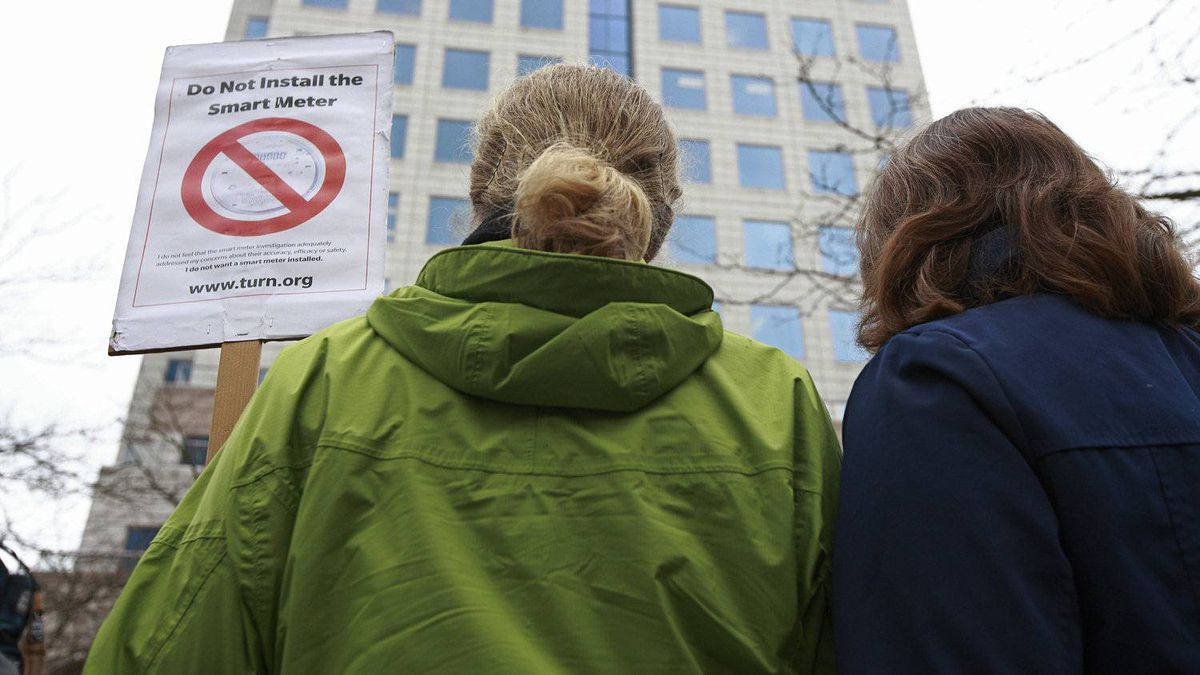 Two women stand below BC Hydro headquarters as they protest BC the use of smart meters in Vancouver, BC, February 29, 2012.