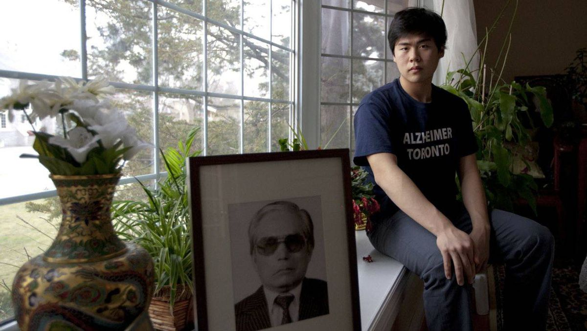 Soojeong Choe, 17, who started an Alzheimer's disease club at his school shortly after his grandfather passed away, poses for a portrait with a photo of his grandfather.
