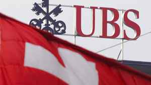 Two Swiss flags fly above a logo of the UBS on the top of the Swiss banking giant headquarters, on November 15, 2008 in Zurich.
