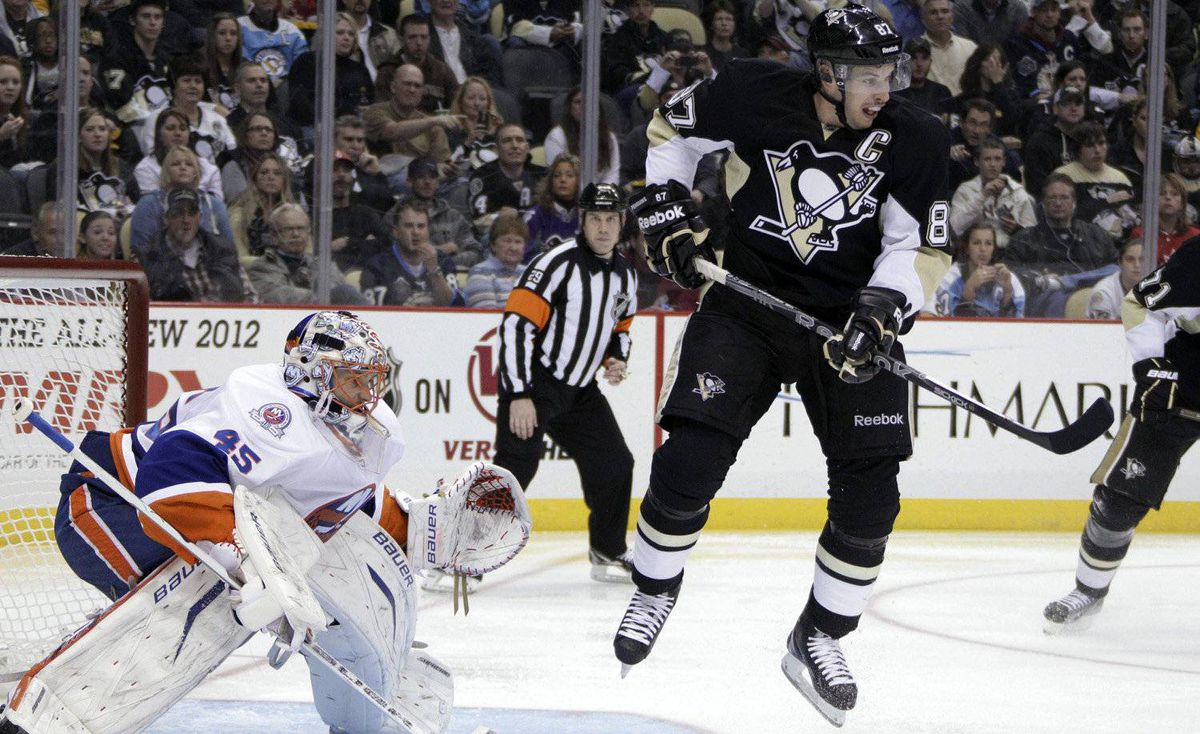 Pittsburgh Penguins' Sidney Crosby leaps out of the way of a shot in front of New York Islanders goalie Anders Nilsson during the second period of an NHL hockey game against the New York Islanders in Pittsburgh on Monday, Nov. 21, 2011.
