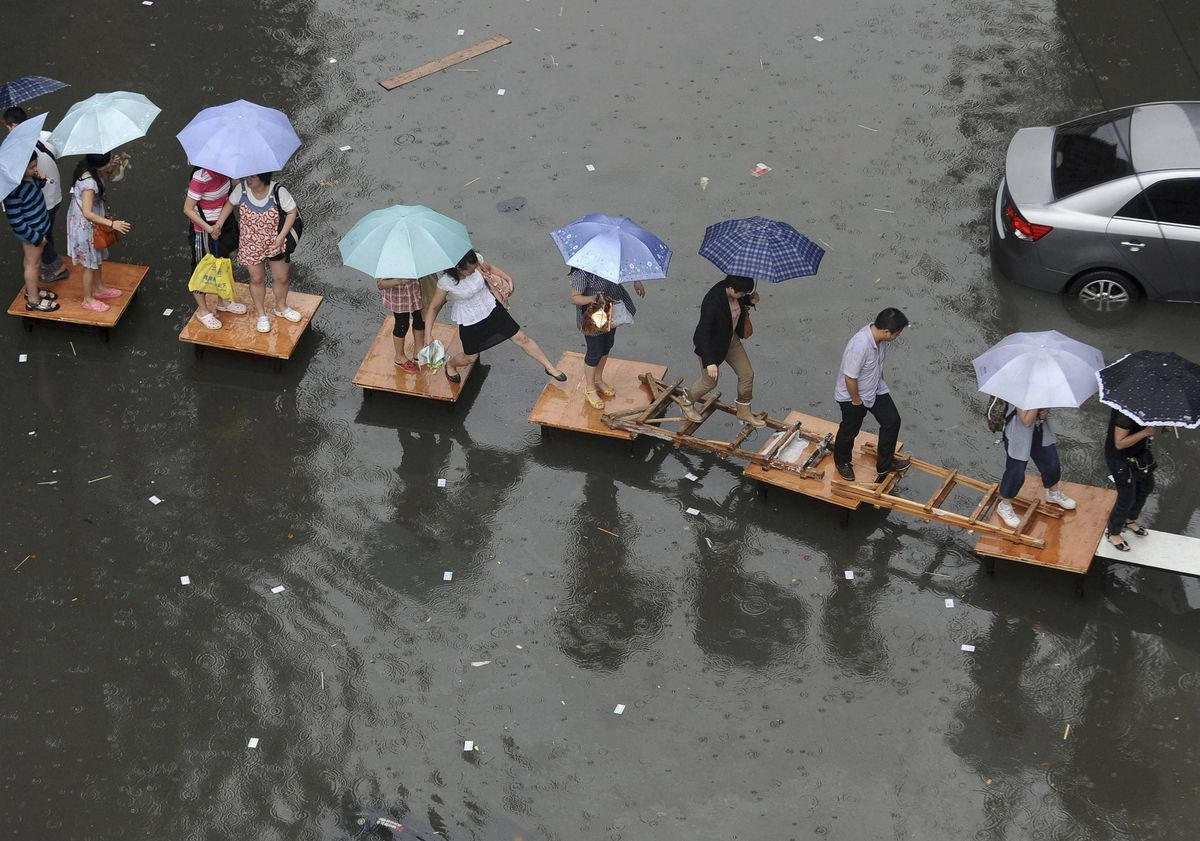People hold umbrellas as they cross a flooded street by stepping on wooden tables and ladders amid heavy rainfalls in Wuhan, Hubei province, China.