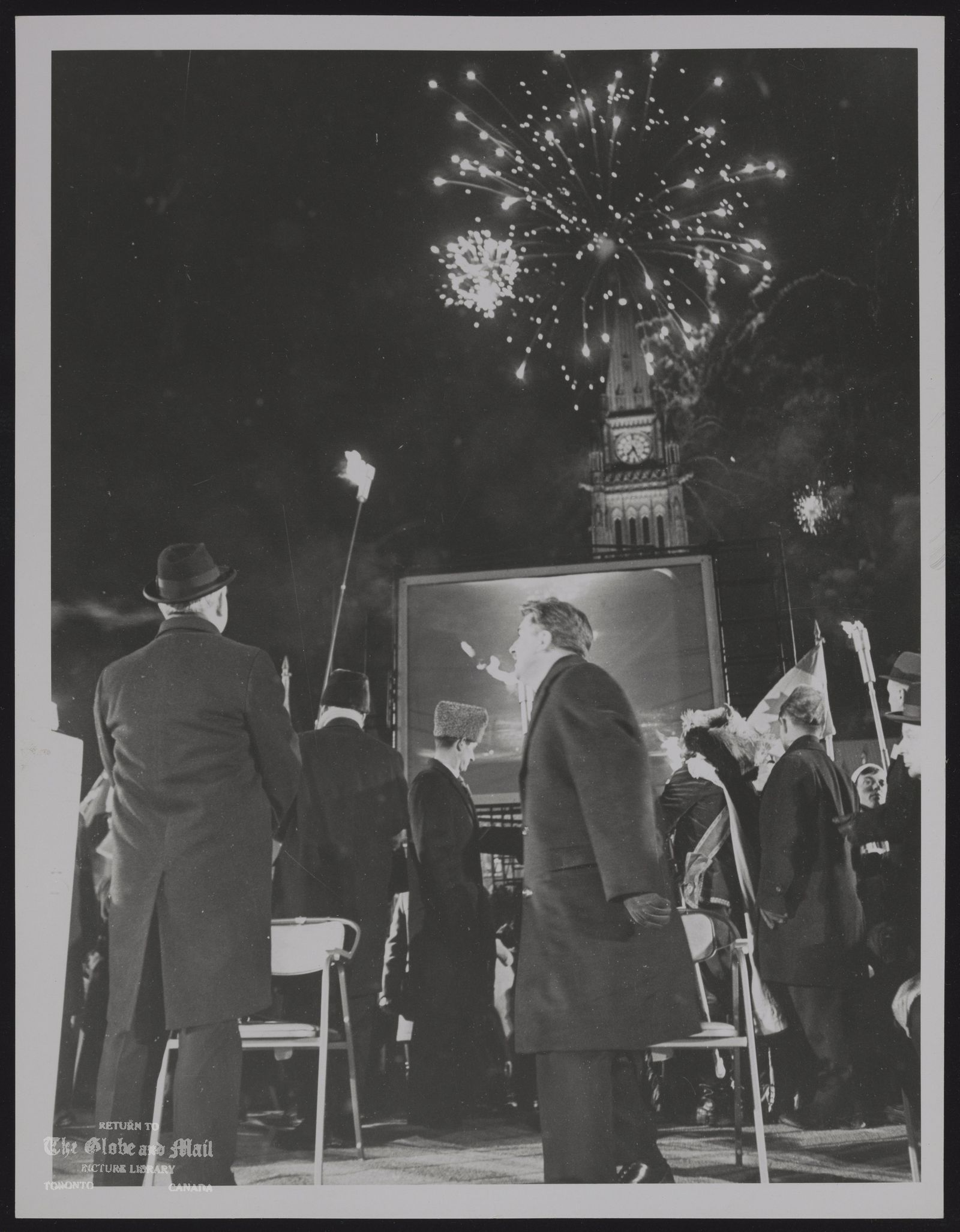 CANADA dominion Centennial Prime Minister Lester Pearson and Jean Marchand watch fireworks burst over Peace Tower in Centennial ceremony on Parliament Hill on New Year's Eve as Opposition Leader John Diefenbaker (extreme right) looks on.