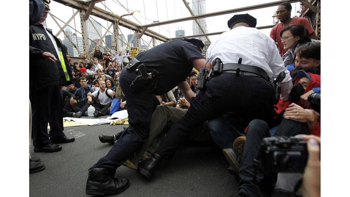 Police officers reach into a crowd of protesters to make an arrest on the Brooklyn Bridge during an Occupy Wall Street march in New York October 1, 2011.