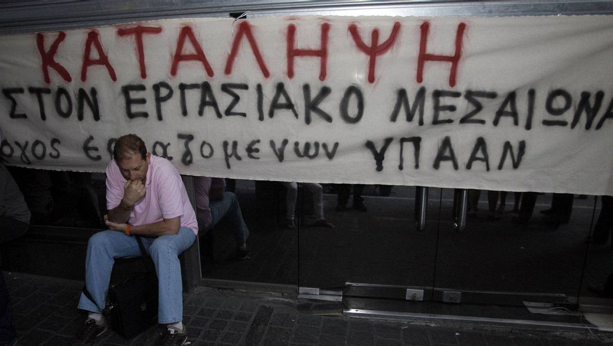 A protester sits in front the entrance of the Finance Ministry during a blockade by employees in Athens on Sept. 29, 2011.