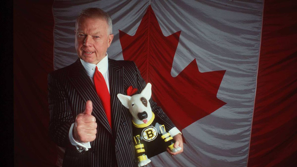 Don Cherry poses in front of the Canadian flag with a Boston Bruin dog during a photo shoot