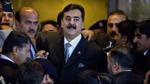 Pakistani Prime Minister Yousuf Raza Gilani is surrounded by security personnel as he arrives at the Supreme Court for a hearing, in Islamabad on Feb. 13, 2012.