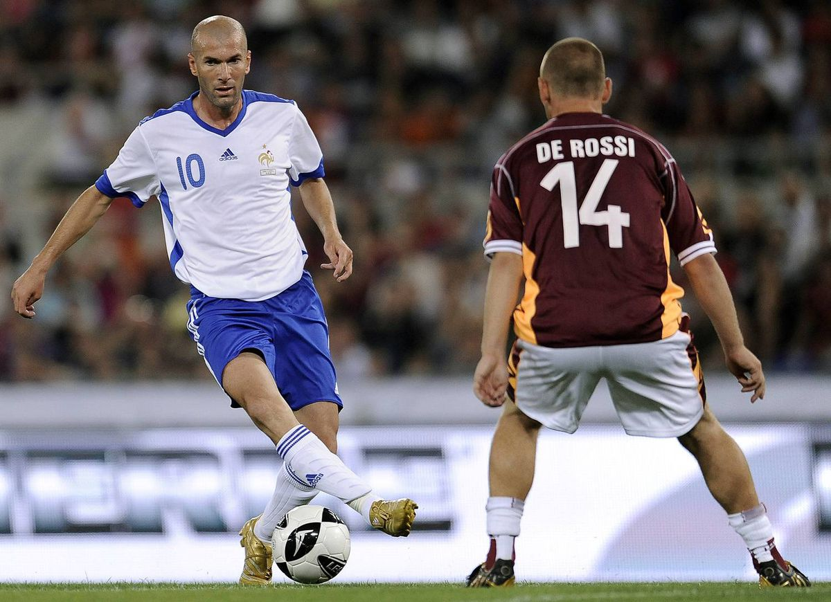 France forward Zinedine Zidane, left, vies with AS Roma'sDaniele De Rossi during French defender Vincent Candela's farewell football match at Rome's Olympic Stadium on June 06, 2009.