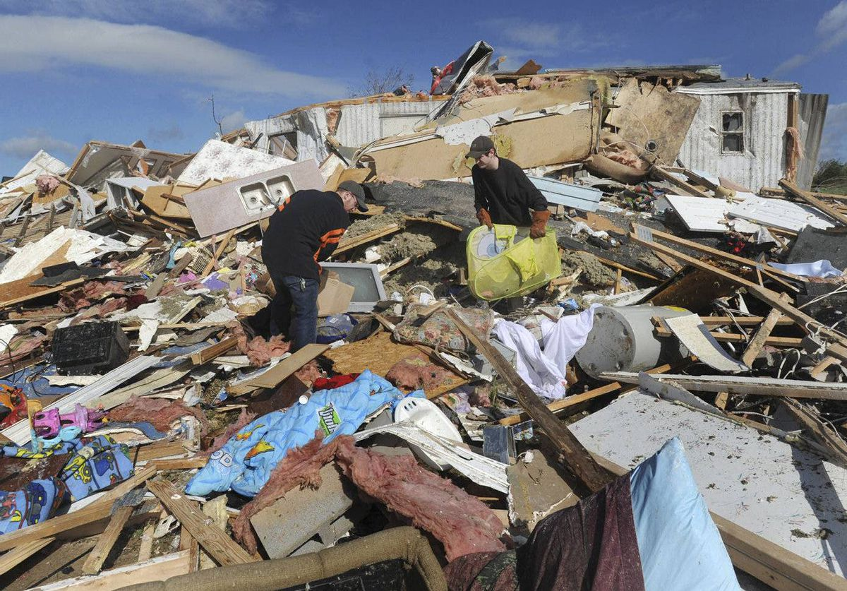 Kasey Dillon, left, and Daniel Snider, right, look through the debris of a friend's home after a severe thunderstorm in Glade Springs, Va. Gov. Bob McDonnell declared a state of emergency Thursday.