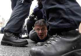 A man is detained by riot police during demonstrations in north Dublin against the visit by Britain's Queen Elizabeth.