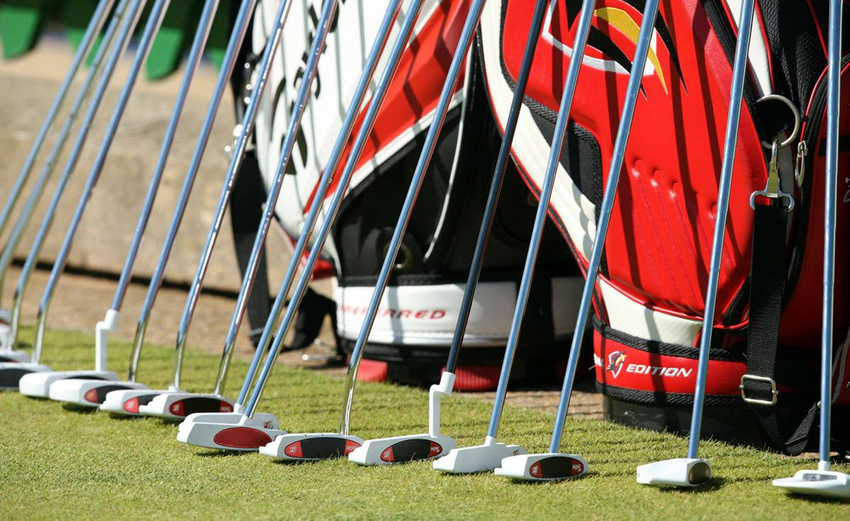 A row of putters stands alongside the practice green at the Old Course, St. Andrews