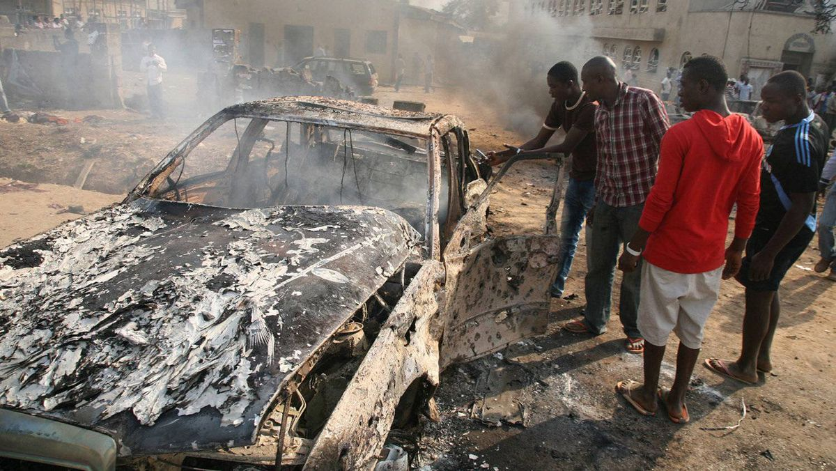Men look at the wreckage of a car following a bomb blast at St Theresa Catholic Church outside the Nigerian capital Abuja on December 25, 2011. Two explosions near churches during Christmas Day services in Nigeria, including one outside the country's capital, killed at least 25 people amid spiralling violence blamed on an Islamist group. The suspected attacks stoked fear and anger in Africa's most populous nation, which has been hit by scores of bombings and shootings attributed to Islamist group Boko Haram, with authorities seemingly unable to stop them.