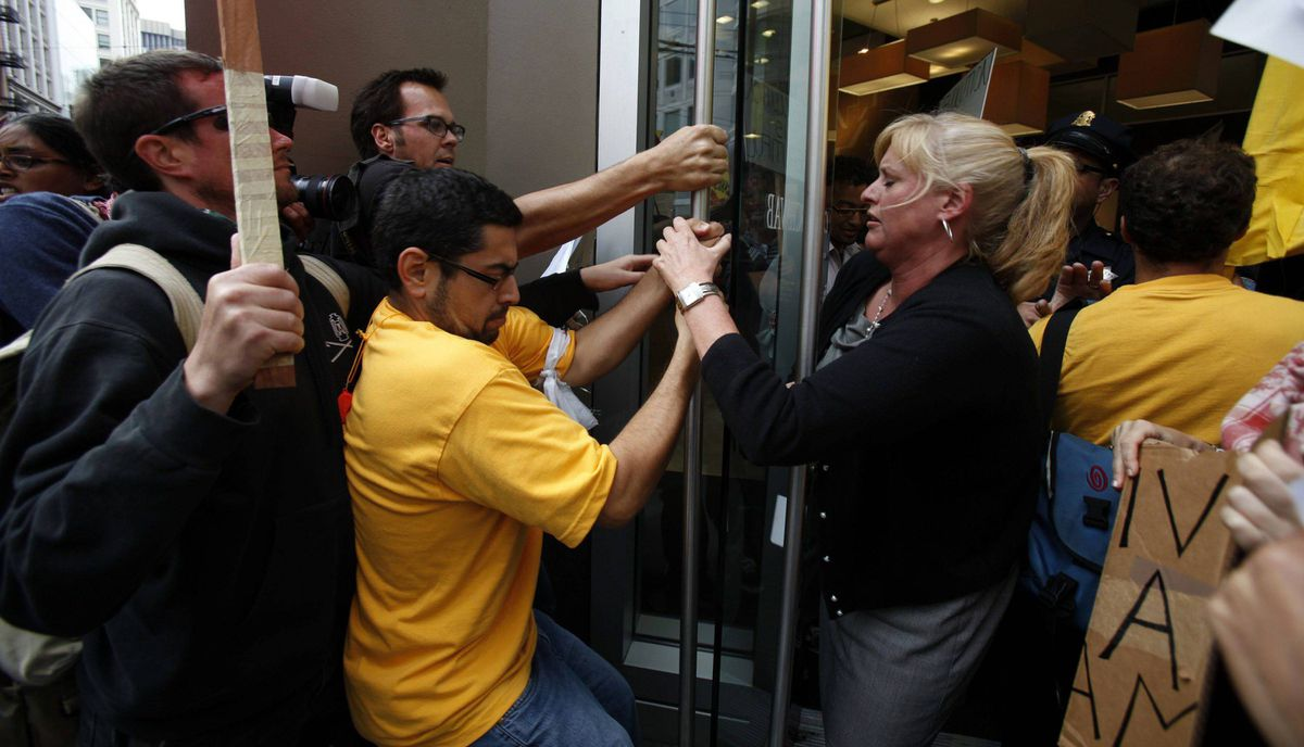 A group of demonstrators scuffles with a Charles Schwab employee at the door during a rally against banking institutions as part of the Occupy Wall Street campaign in San Francisco, California September 29, 2011.