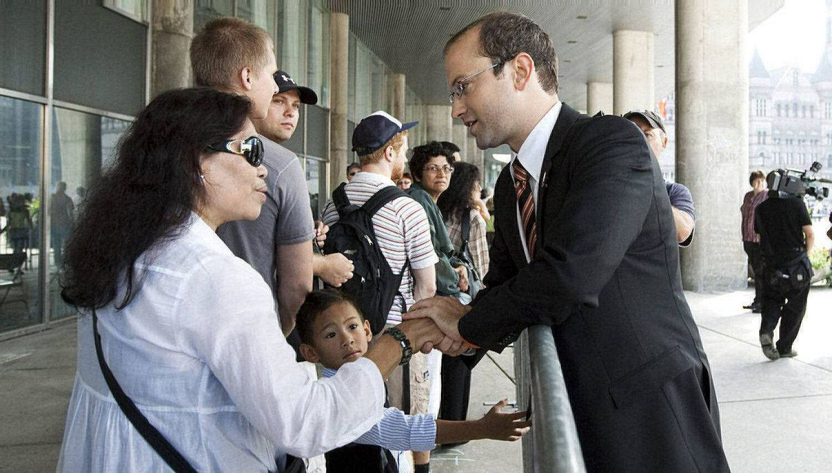 Mike Layton, son of Jack Layton, right, greets people in line at Nathan Phillips Square prior to the funeral of the late NDP leader.