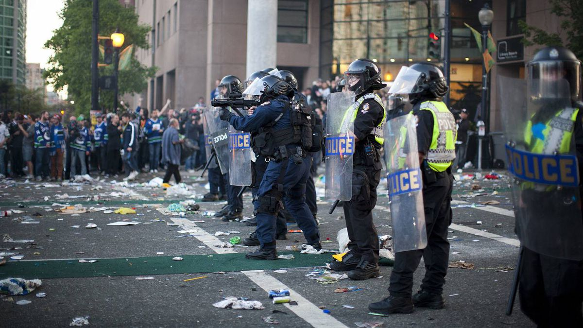 Vancouver riot police fire tear gas at Hamilton Street and Georgia Street after the Boston Bruins won the Stanley Cup.