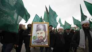 "Members of Islamist group ""al-Gama'a al Islamiya"", carry their party's flags and a picture of Hassan Al-Banna, the Muslim Brotherhood founder, during a demonstration against Egypt's President Hosni Mubarak in front of the Egyptian Embassy in Beirut, February 4, 2011."