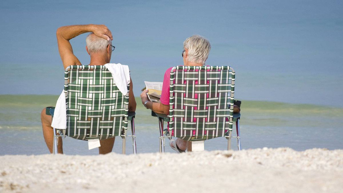 Two senior citizens enjoy the early morning calm of the Gulf of Mexico at Bonita Beach, Florida.