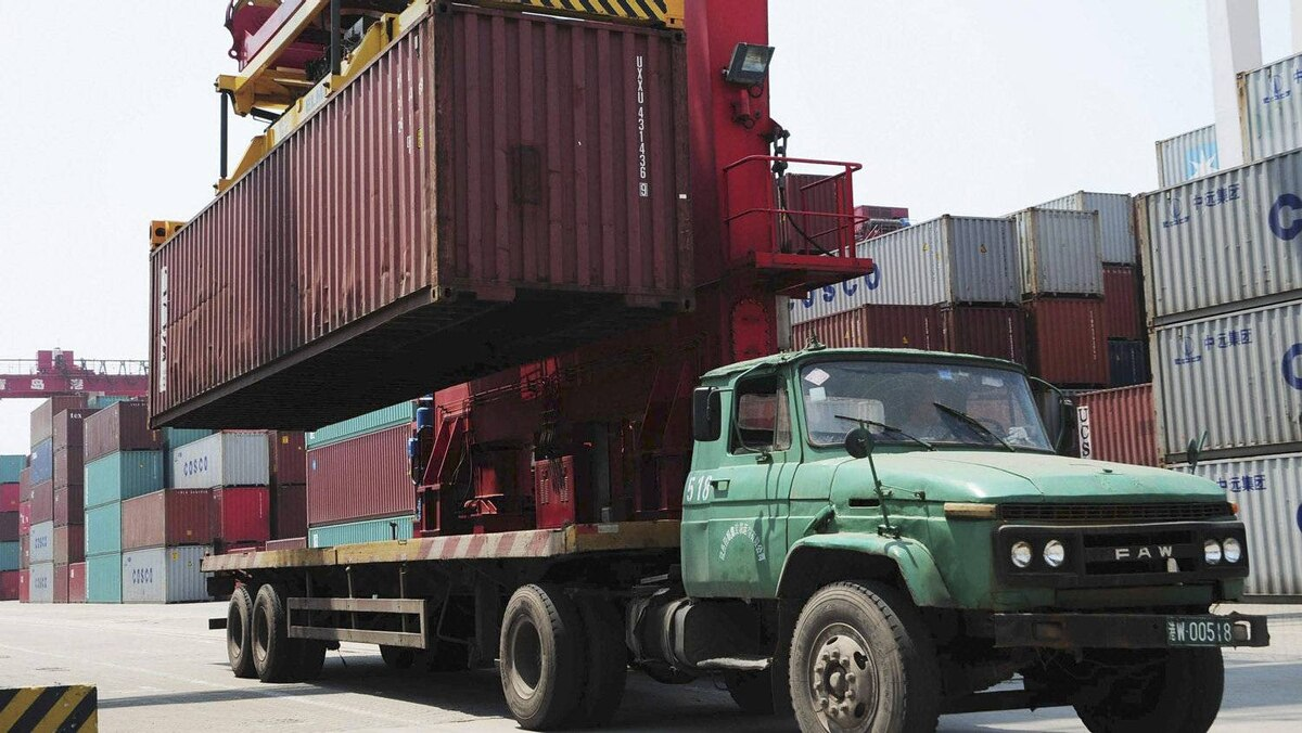 A crane loads a container onto a truck at a port in Qingdao, Shandong province, on May 10, 2012.