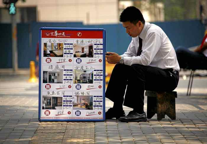 A real estate agent sits next to a board displaying prices for residential apartments in central Beijing. Home prices are falling in the Asian nation.